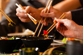 Four sets of chopsticks grabbing Asian food out of various black bowls sitting on a table in a Thai food restaurant.  Three pairs of chopsticks have food between them, and one is in a black bowl.  The