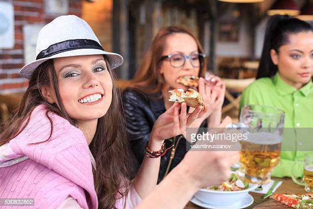 Young people eating pizza and drinking beer at restaurant