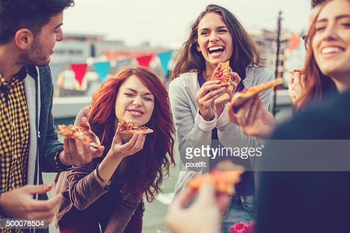 Young people eating pizza at party