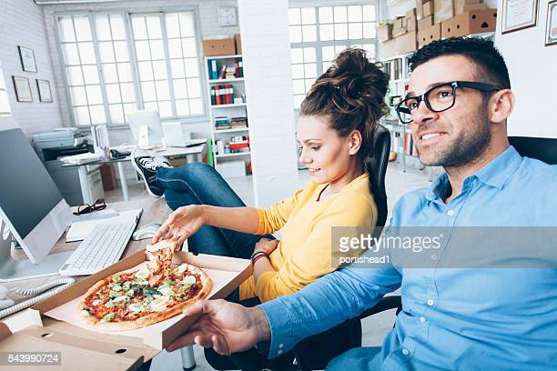Young people eating pizza at workplace