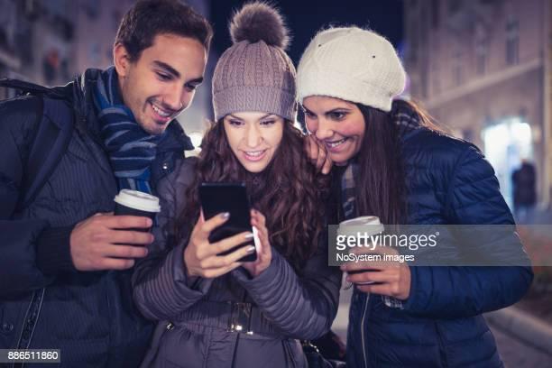 若い人たちの屋外で、楽しい友達見てソーシャル メディアの投稿は、スマート フォンで