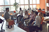 young people group in modern office have team meeting and brainstorming while working on laptop and drinking coffee.
