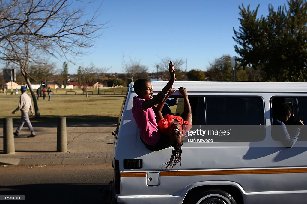 Young people hang out of a taxi window as they make their way to a youth day pre celebration in Soweto on June 15, 2013 in Johannesburg, South Africa. It has been reported that Nelson Mandela is responding better to treatment for a recurring lung infection.