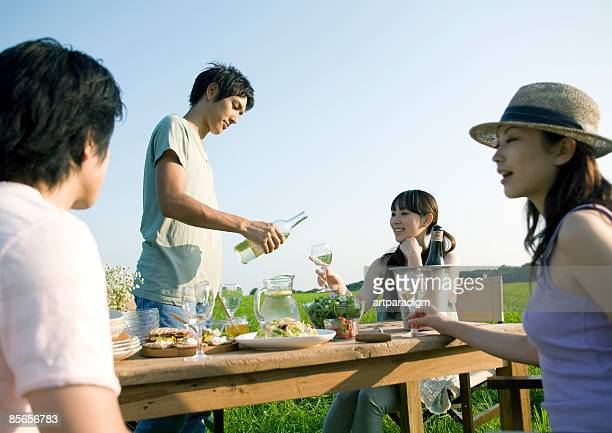 Young people having a picnic in field