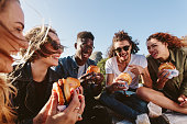Young people having summer picnic and eating together sitting on mountain top. Happy friends on mountain top having a picnic on a summer day.