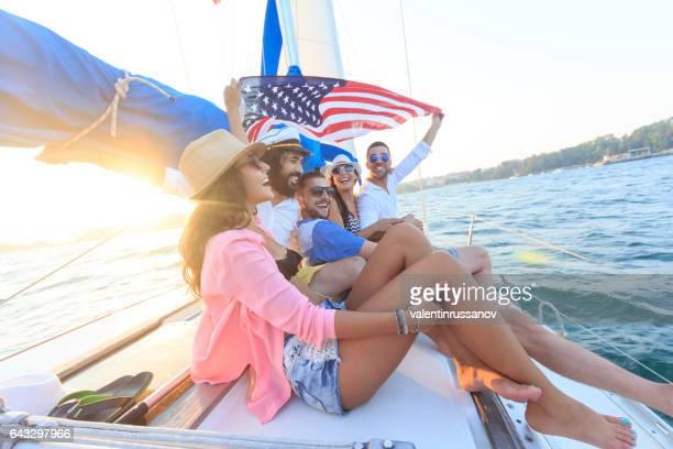 Jonge mensen met plezier en zeilen in zee