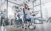 Young cheerful business people dressed in casual clothing are having fun on rowing chairs in a modern office. Happy team concept.
