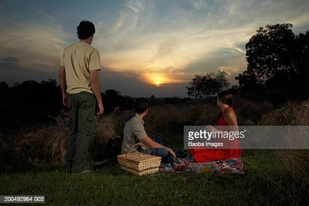 Young people having picnic, watching sunset