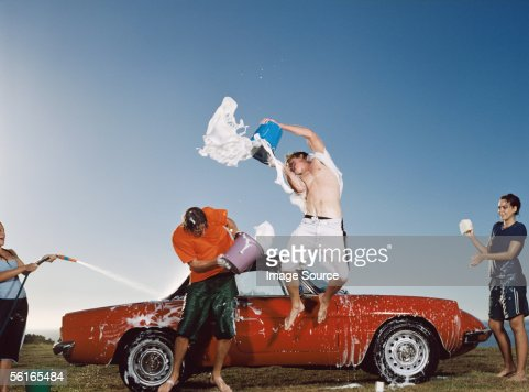 Young people having water fight and washing car