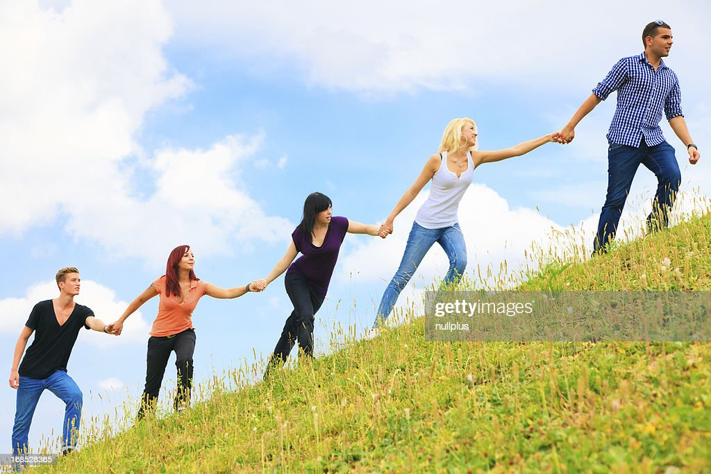 Young People Helping Each Other Climb A Hill Stock Photo ...