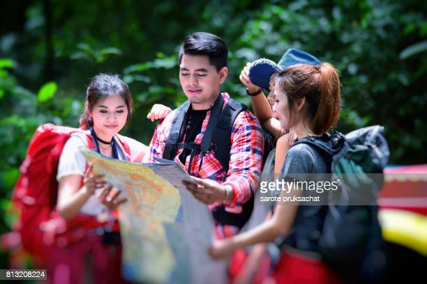 Young people hikers in forest with backpack holding a map in the countryside .Camp Forest Adventure Travel Remote Relax Concept .