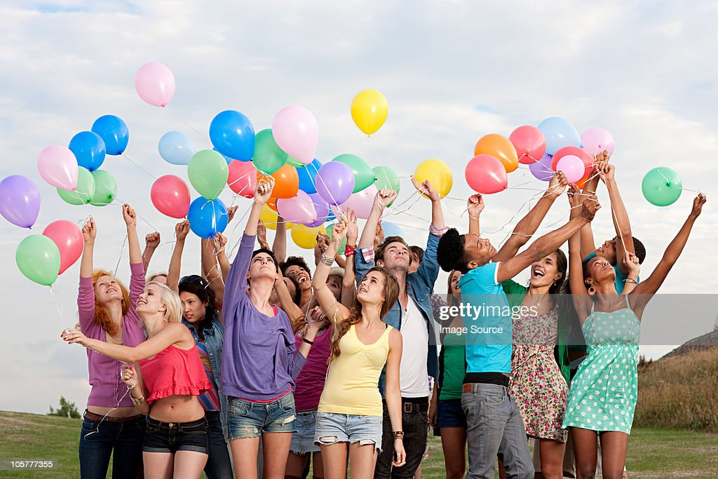 Young people holding balloons : Stock Photo