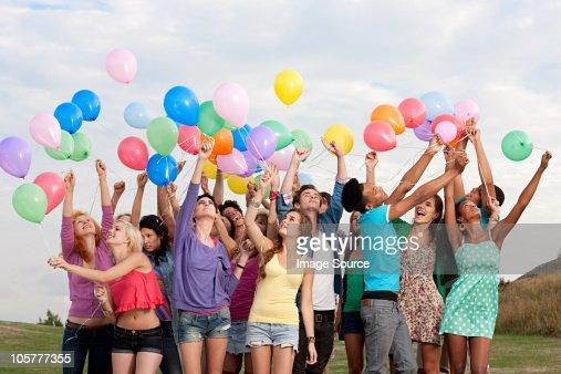 Jóvenes sostiene los globos : Foto de stock