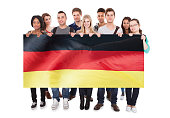 Group Of Young People Holding German Flag Against White Background