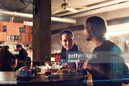 Young people in a club having drink and snack