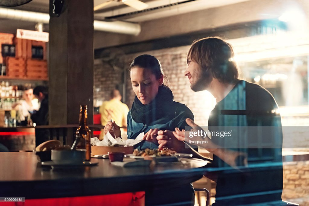 Young people in a club having drink and snack : Stock Photo