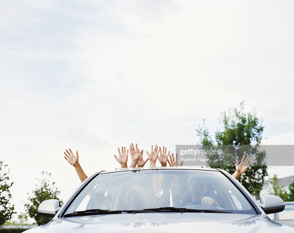 Young people in car sticking arms through sun roof and windows : Stock Photo