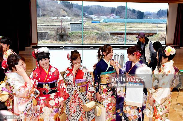 Young people in colorful kimono chat during ComingofAge ceremony while a mound of contaminated soil is seen outside on January 8 2017 in Iitate...