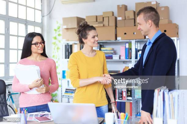 Young people in handshake at the office