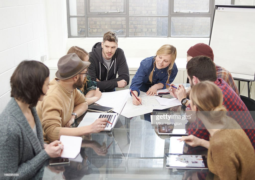 Young people in meeting exchanging ideas : Stock Photo