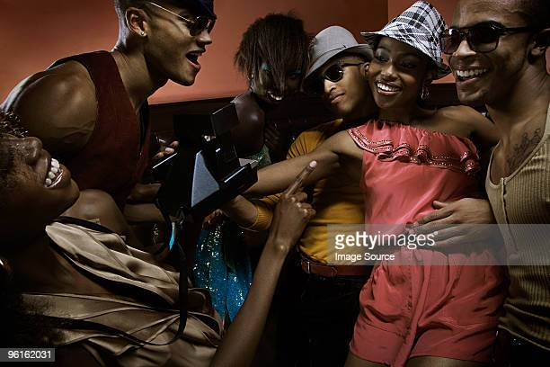 Young people in nightclub with instant camera