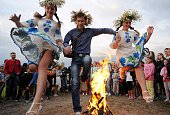 Young people jump over a bonfire as they take part in the Ivan Kupala Night celebration a traditional Slavic holiday outside the small town of Turov...
