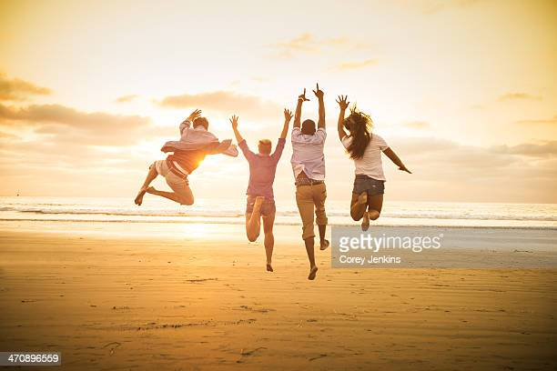 Young people jumping on Mission Beach, San Diego, California, USA