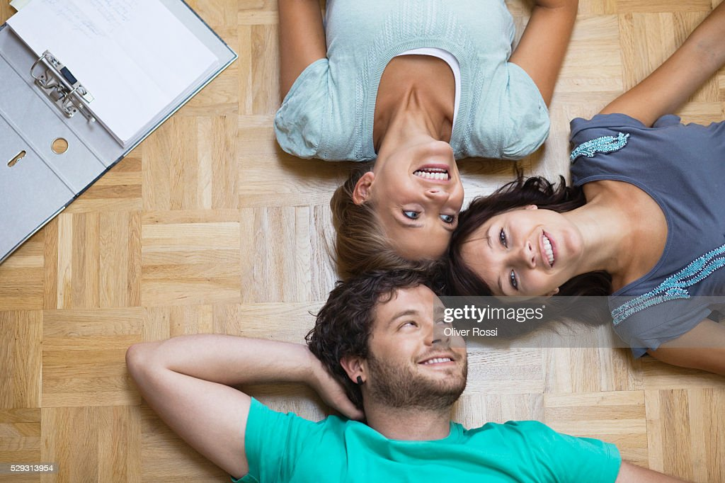 Young people lying on floor : Stock Photo