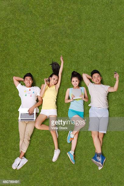 Young people lying on grass looking at phone and tablet