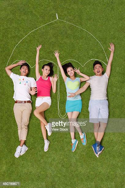 Young people lying on grass under an artificial umbrella