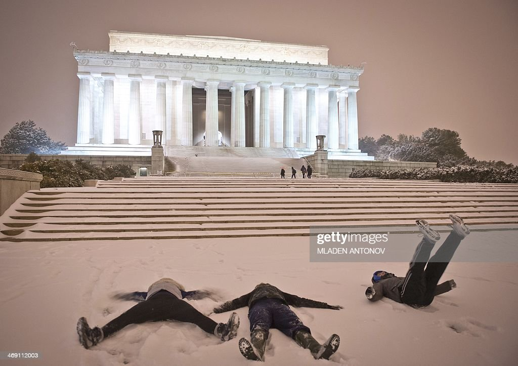 Young people make 'snow angel' shapes in the snow in front of the Lincoln Memorial as a heavy snow storm hits Washington DC on February 13 2014 The...