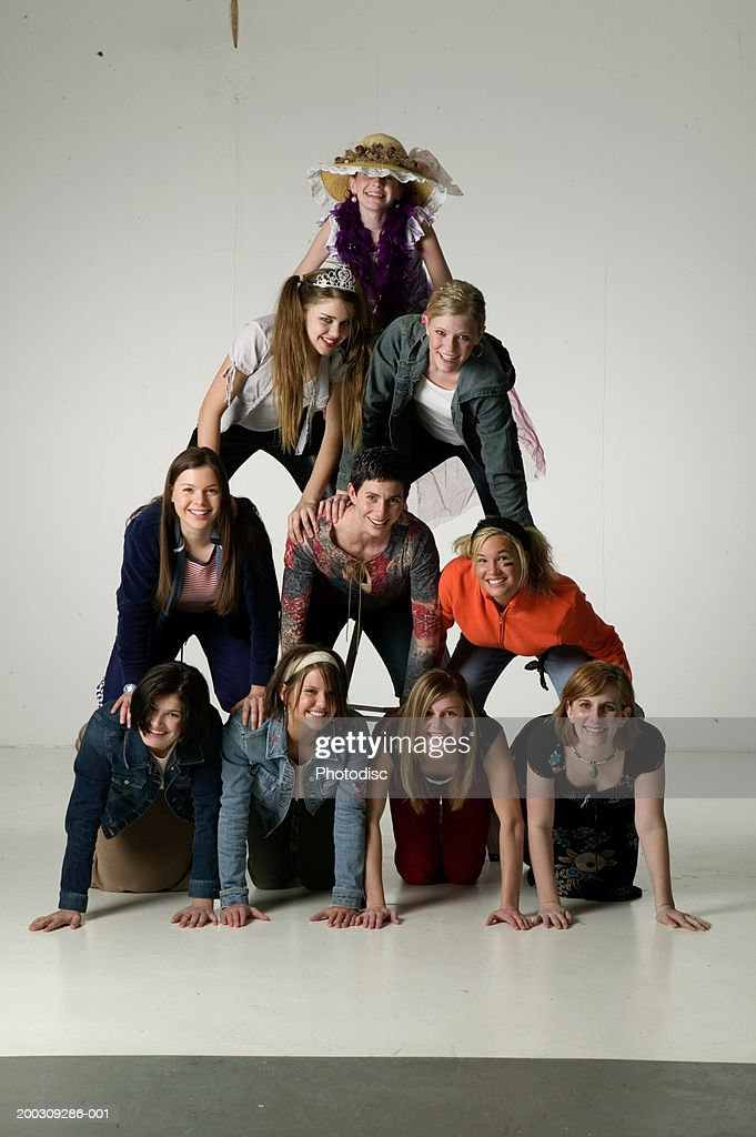 Young people making human pyramid, in studio, portrait