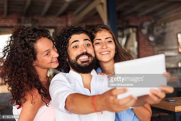 Young people making selfie at bar with digital tablet
