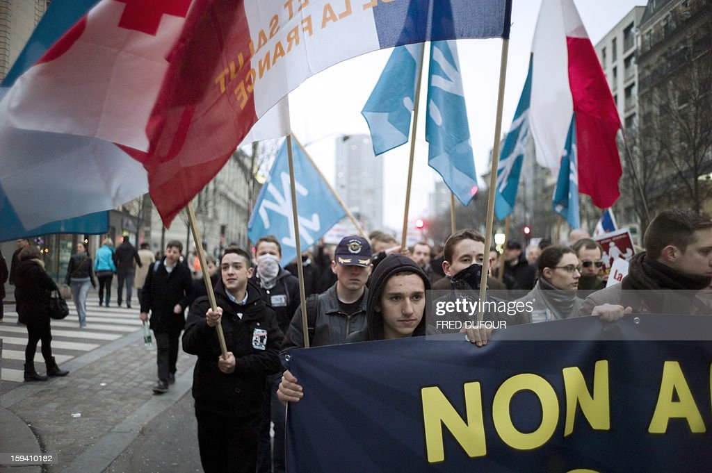 Young people of the 'Renouveau francais' (French renewal, Nationalist) hold flags of their movement as they take part in a march against same-sex marriage on January 13, 2013 in Paris. Tens of thousands march in Paris on January 13 to denounce government plans to legalise same-sex marriage and adoption which have angered many Catholics and Muslims, France's two main faiths, as well as the right-wing opposition. The French parliament is to debate the bill -- one of the key electoral pledges of Socialist President -- at the end of this month.