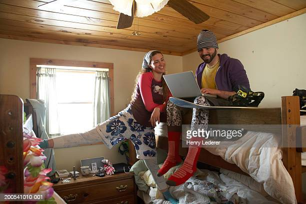 Young people on bunk beds in lodge using laptop