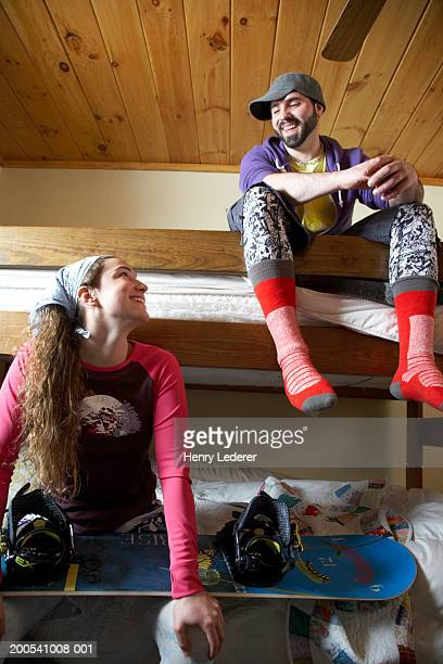 Young people on bunk beds smiling, woman with snowboard