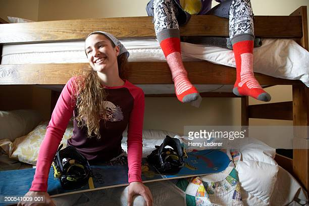 Young people on bunk beds, woman smiling with snowboard on lap