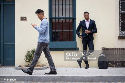 Young people outdoors on the city streets in springtime.  A man leaning against a wall and one walking past checking his phone.