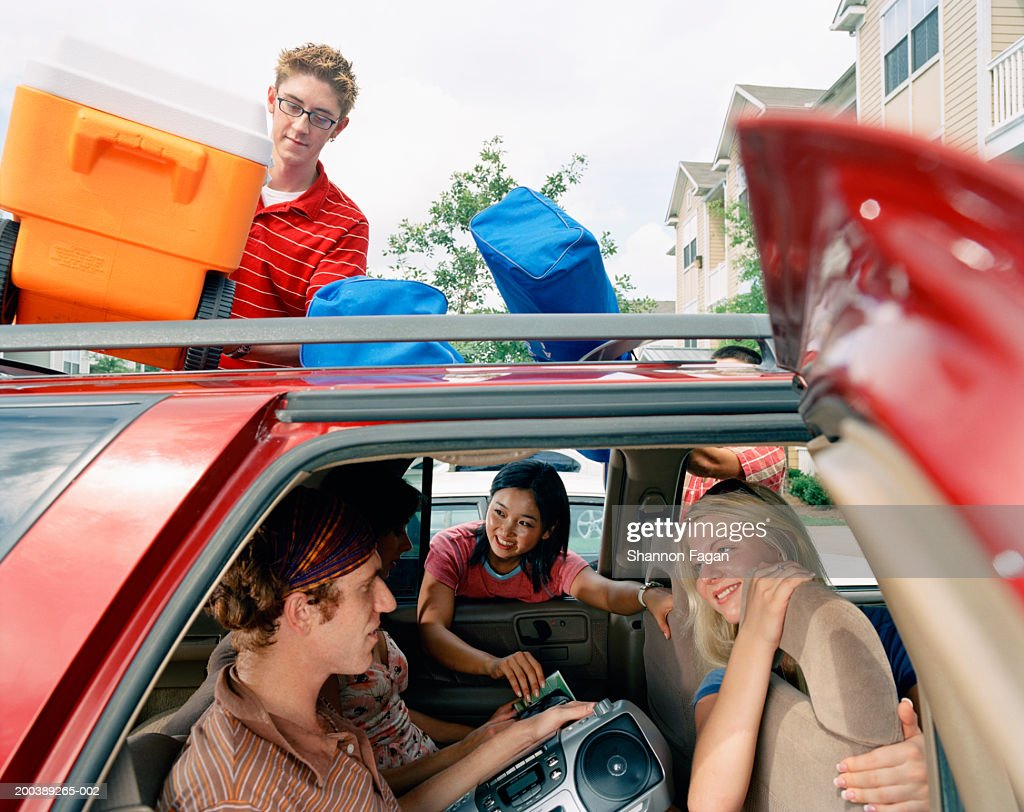 Young people packing car for roadtrip : Stock Photo