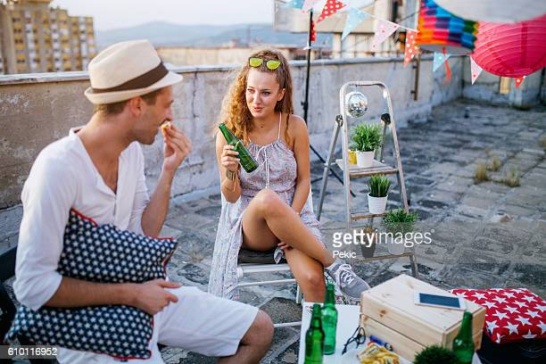 Young people partying on terrace with drinks at sunset