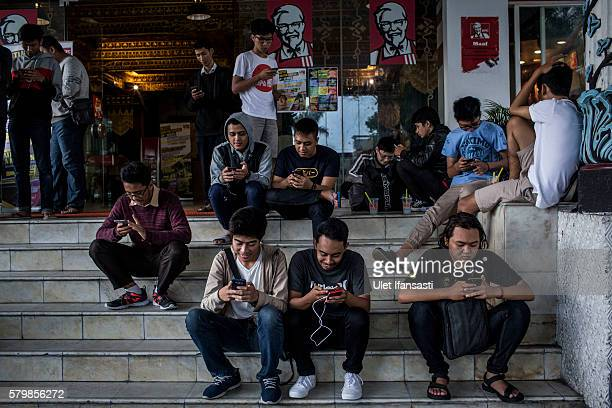Young people play Pokemon Go game on smartphones in front of a KFC restaurant on July 23 2016 in Yogyakarta Indonesia 'Pokemon Go' which uses Google...