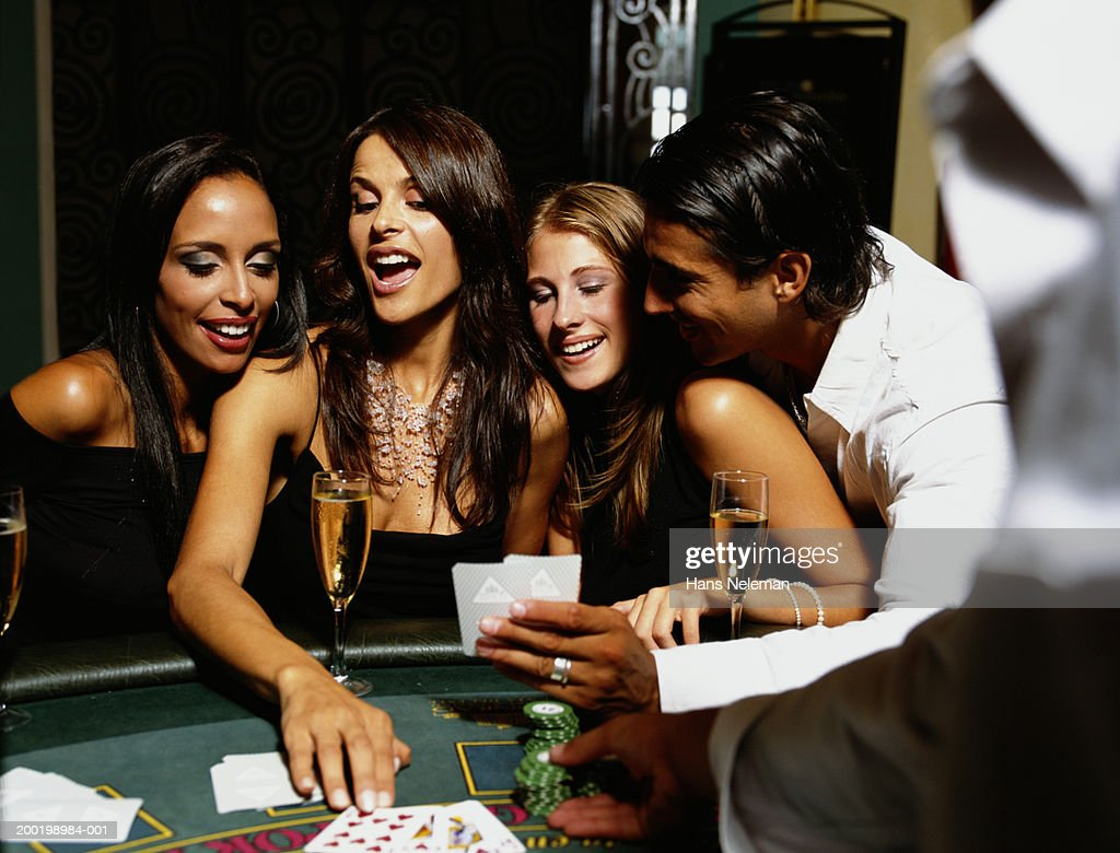 Young people playing cards at casino : Stock Photo