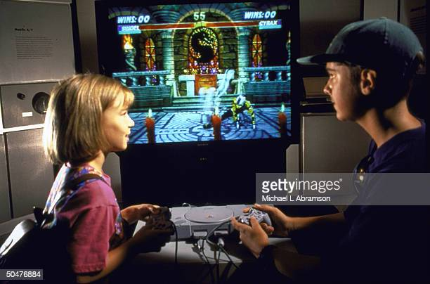 2 young people playing Doom computer game on PlayStation video game system by Sony
