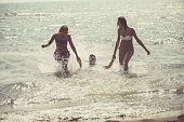 Two girls are dragging their male friend in shallow water. They are fooling around at the beach on a hot summer day.