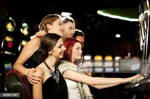 Young people playing slot machines at the Casino : Stock Photo