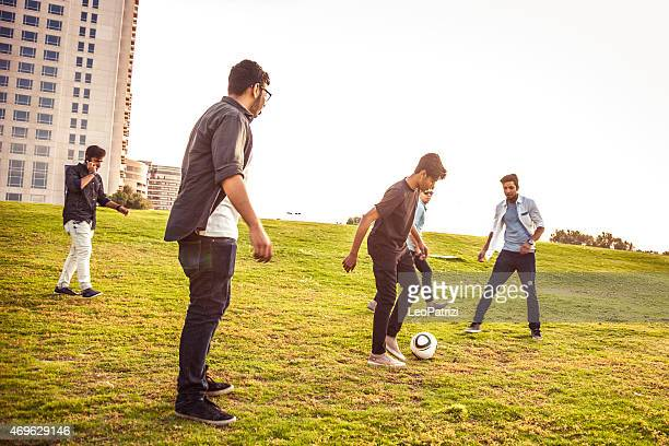 Young people playing soccer in a park