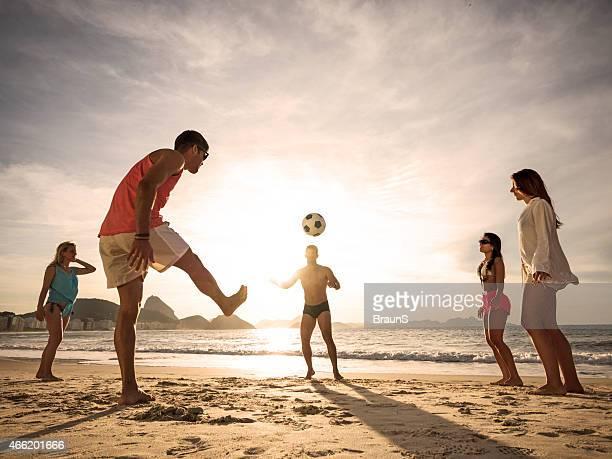 Ragazzi giocare a calcio sulla spiaggia al tramonto.