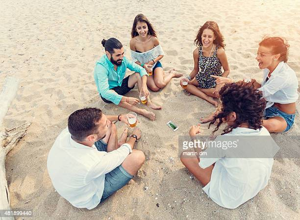 Young people playing spin the bottle at the beach