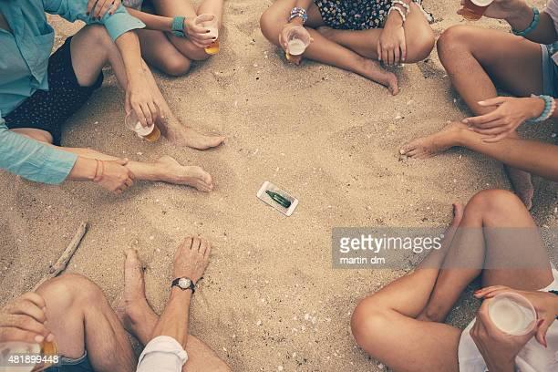 若い人々が「スピンザボトル」のビーチ