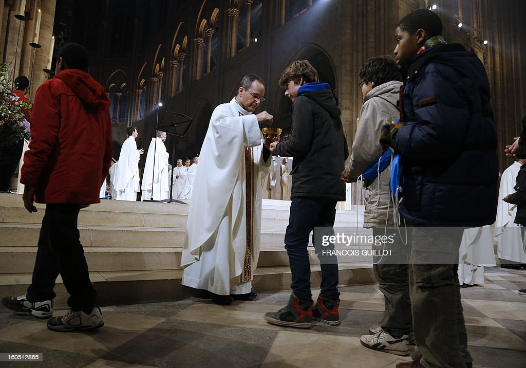Young people receive the eucharist during a mass at Paris' Notre-Dame de Paris Cathedral during which the church's nine new bells have been blessed on February 2, 2013 in Paris. AFP PHOTO / FRANCOIS GUILLOT
